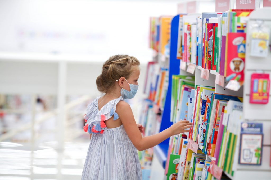 Little girl wearing a mask and reading a book in the library