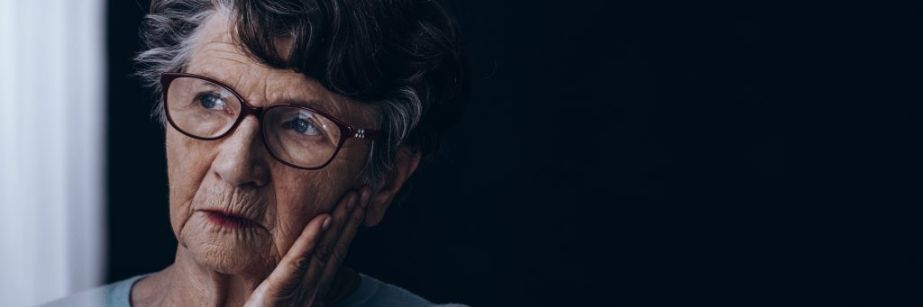 A sad older lady with glasses. How libraries can help with programming on dementia and loneliness