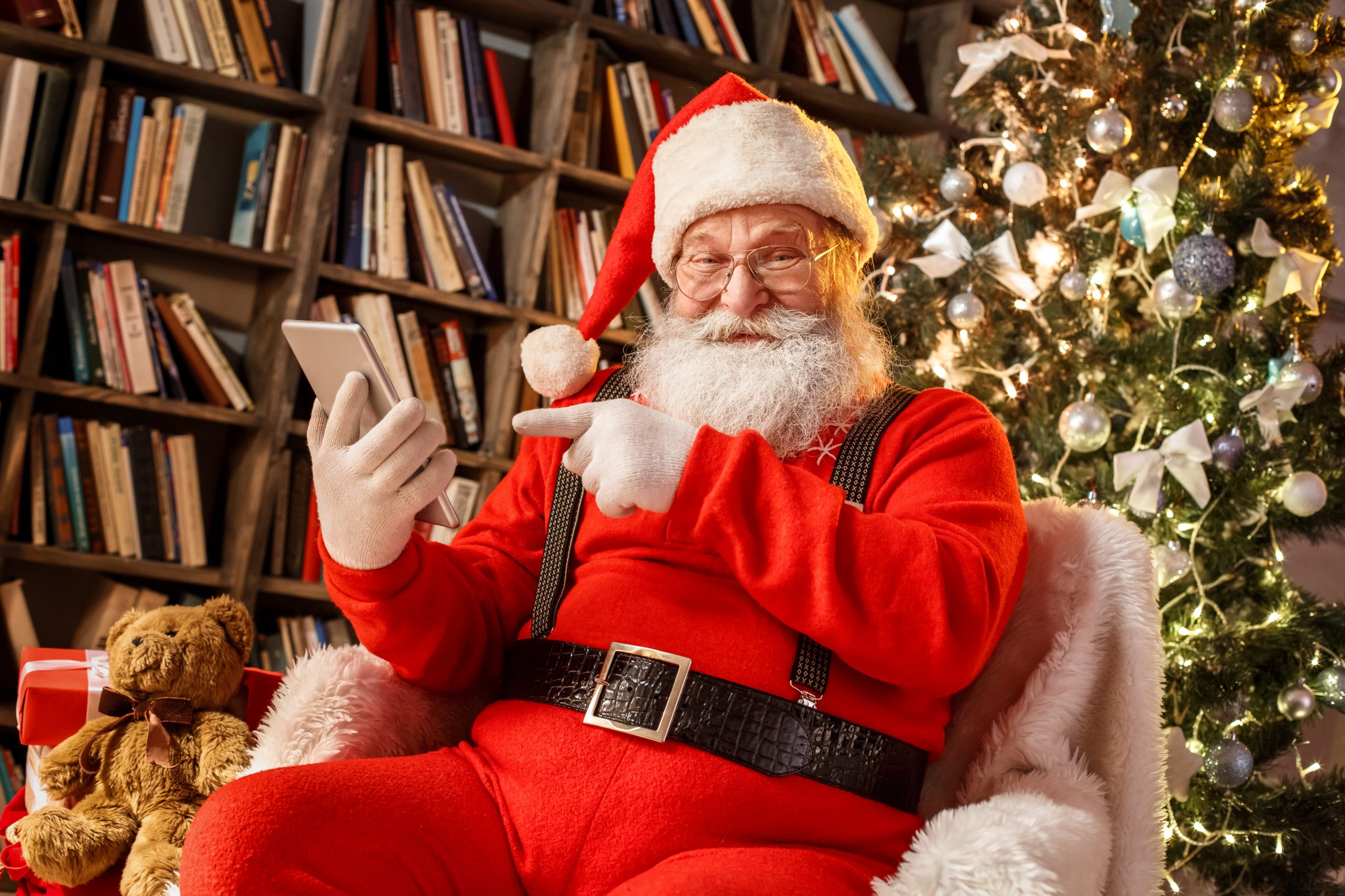 Santa in the library holding a mobile using library app
